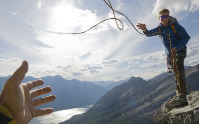Man throwing a rope to a person holding out a hand to catch it