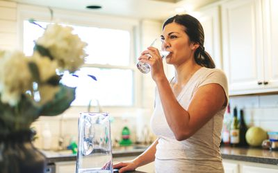woman sipping glass of water in kitchen