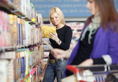Woman reading a food package in a grocery store aisle