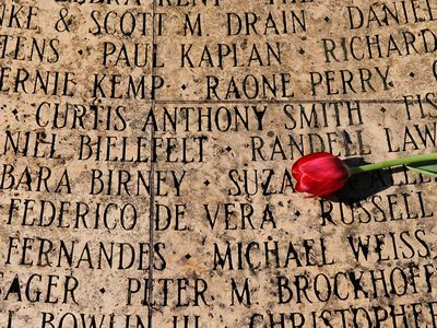 A single tulip rests on the engraved names of people who have died of AIDS on the Circle of Friends memorial before a service at the National AIDS Memorial Grove December 1, 2009 in San Francisco