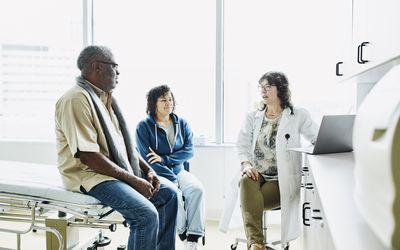 Black man sitting on table talking to white female doctor in brightly-lit exam room