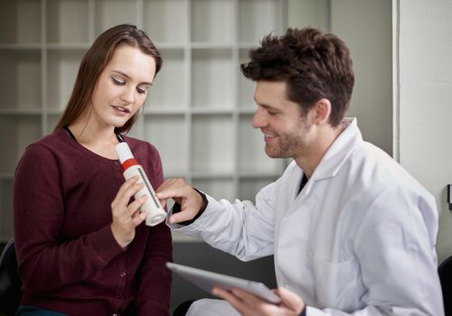 Young woman using peak flow meter and a man assessing results