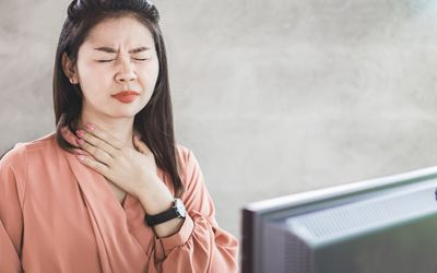 Asian woman suffering from acid reflux or heartburn while working at office desk