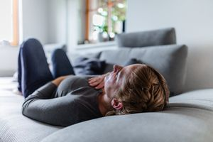 a sick woman lying on the couch