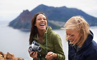 Young happy women traveling with camera in exotic location