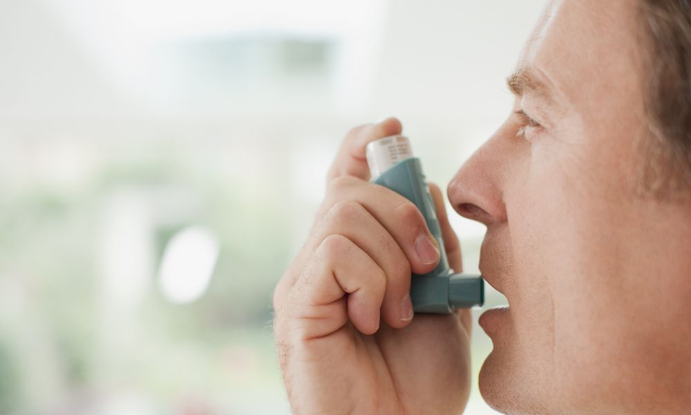 Man about to use asthma inhaler