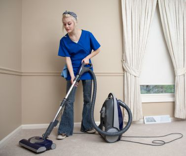 cleaning lady vacuuming floor