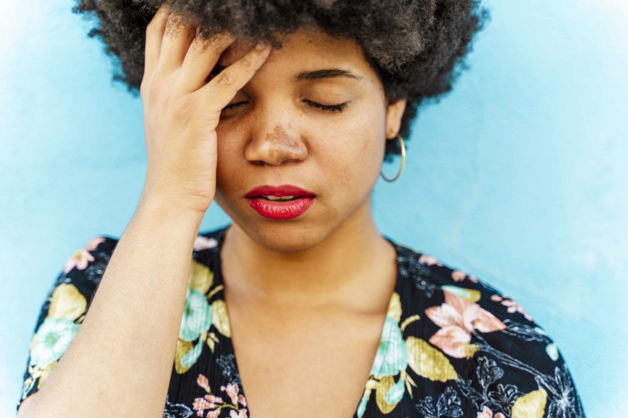 Portrait of Afro-American woman, hand on forehead, blue wall in the background - stock photo