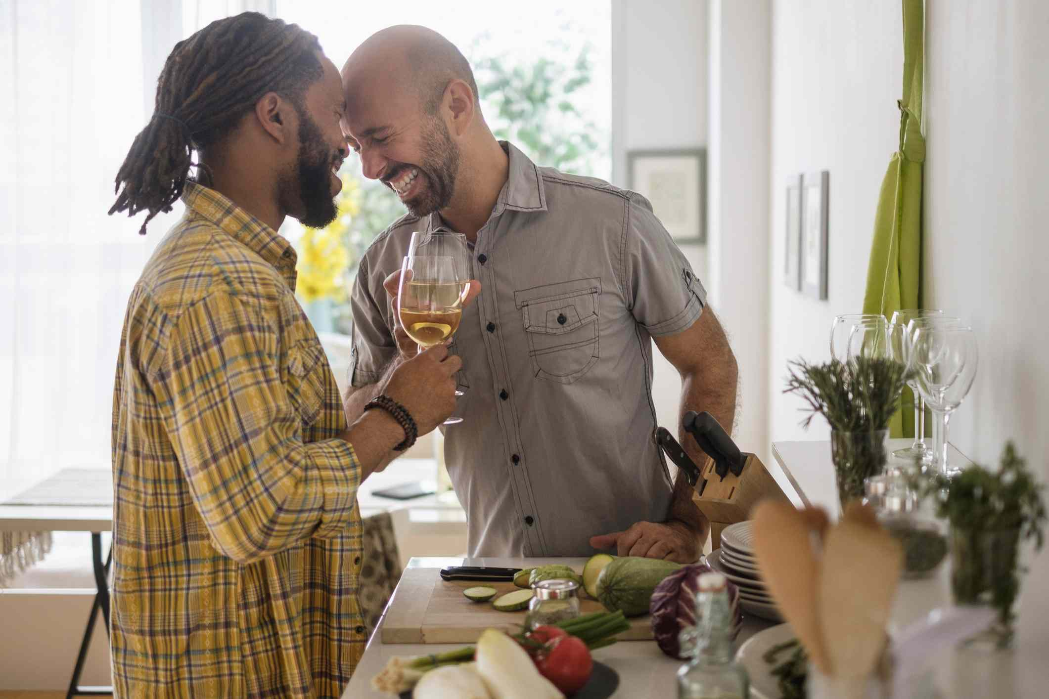 Two men in love having a glass of wine together