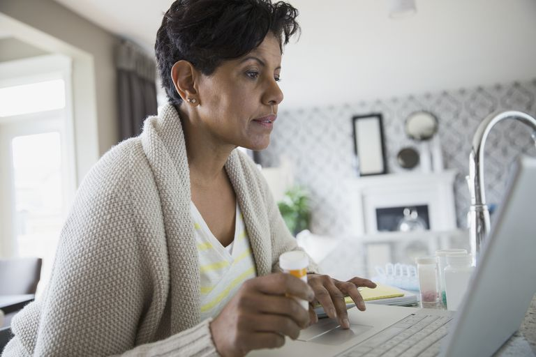 Woman with prescription bottle at laptop