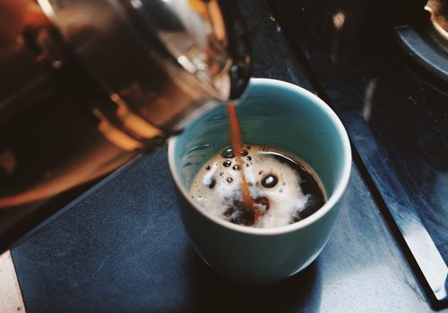 Pouring coffee into a blue cup