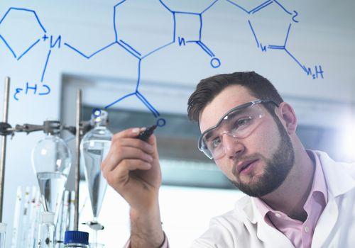 Scientist illustrating an antibiotic chemical formula