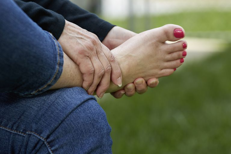 Woman's Hand holding her Foot