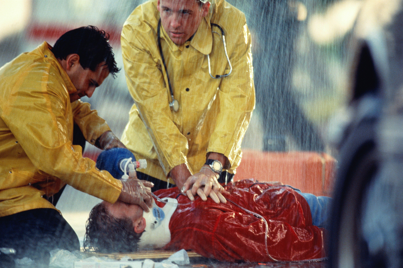 Man in cardiac arrest in the rain with medics preforming CPR