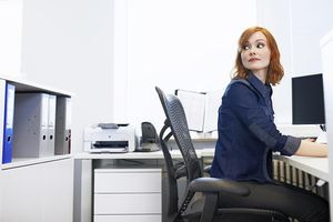 Young businesswoman sitting at a desk looking over her shoulder