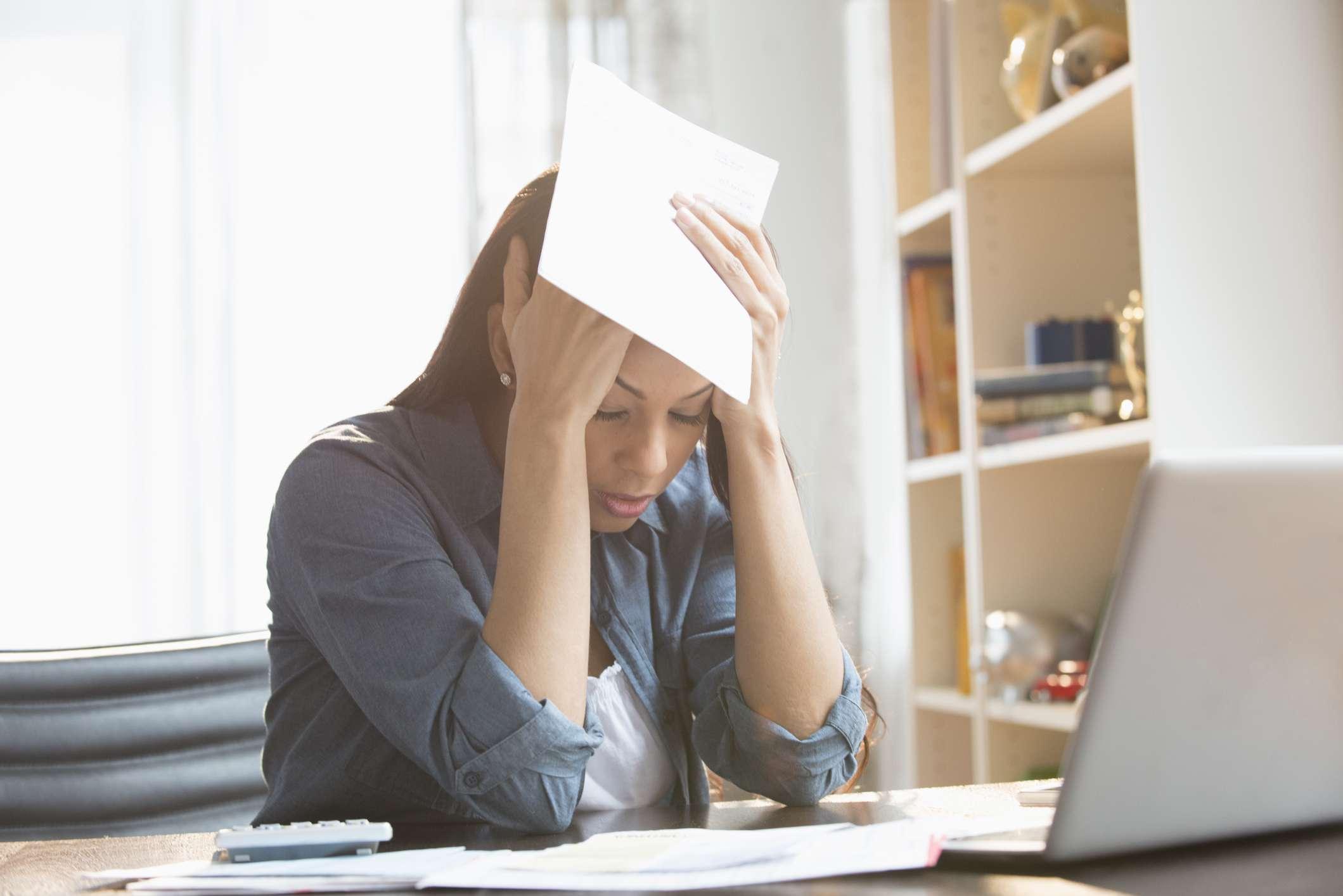 Anxious mixed race woman paying bills on laptop.