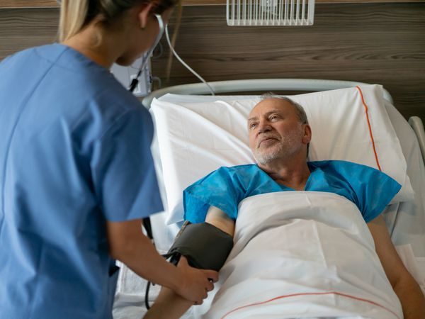Sweet senior man looking at nurse while she checks his blood pressure lying down on hospital bed