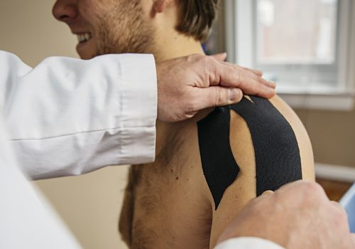 orthopedist applying shoulder tape