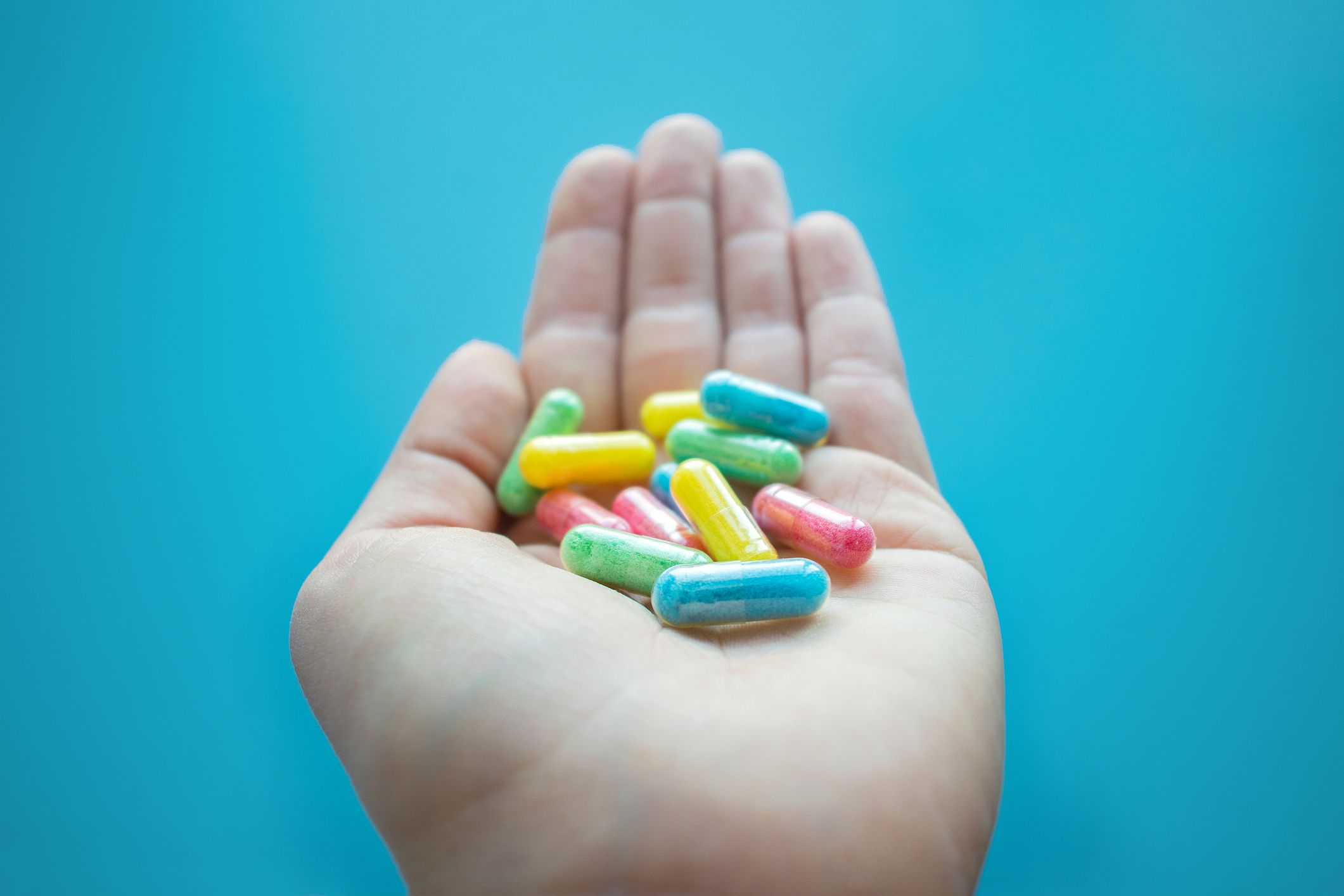 Person holding colorful pills