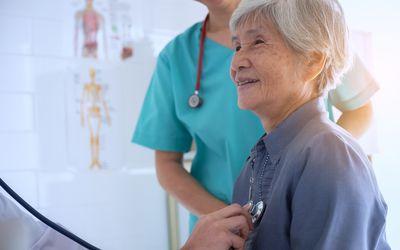 Cropped Hand Of Doctor Examining Senior Woman At Hospital