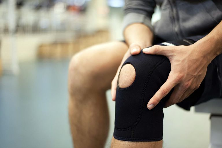 a man holding a brace on his knee