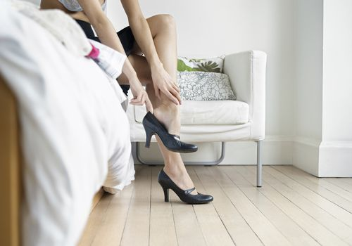 Woman sitting on the edge of a bed taking off high heeled shoes