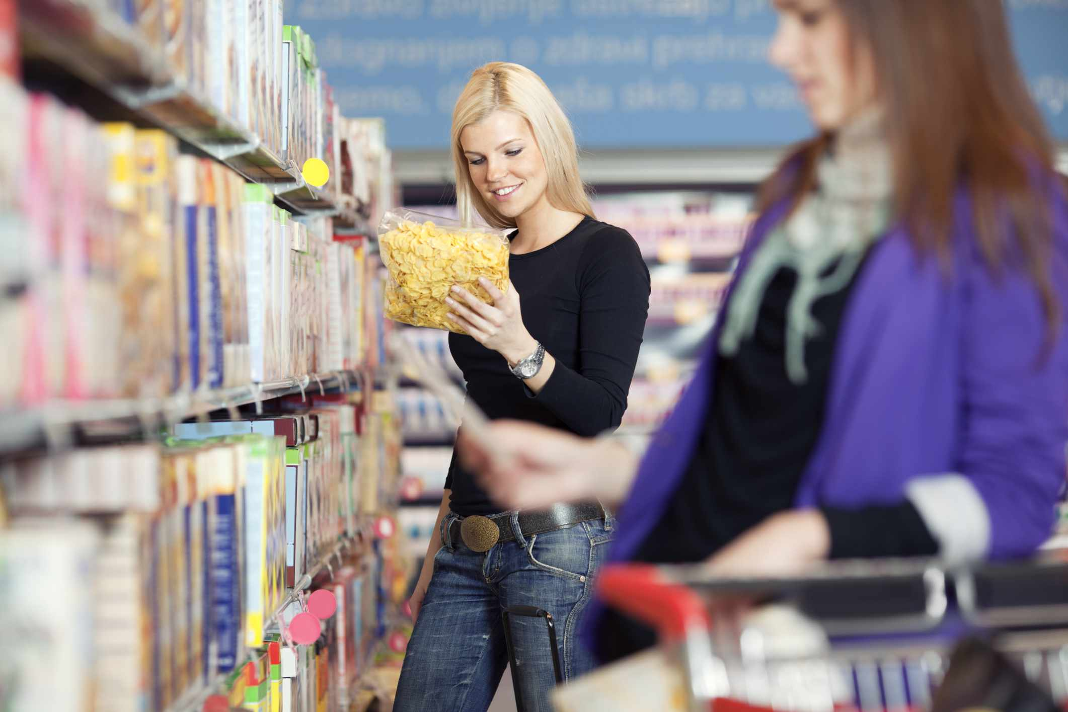 Woman reading package label at grocery store