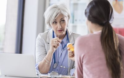 Senior female doctor discusses medication with female patient