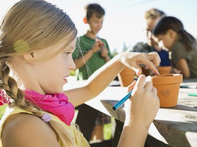 Girl works on summer outdoor craft project.