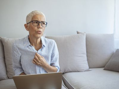 Older woman with glasses sitting on her couch having a hot flash while working on her laptop.