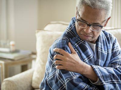 Senior African American man rubbing his shoulder.
