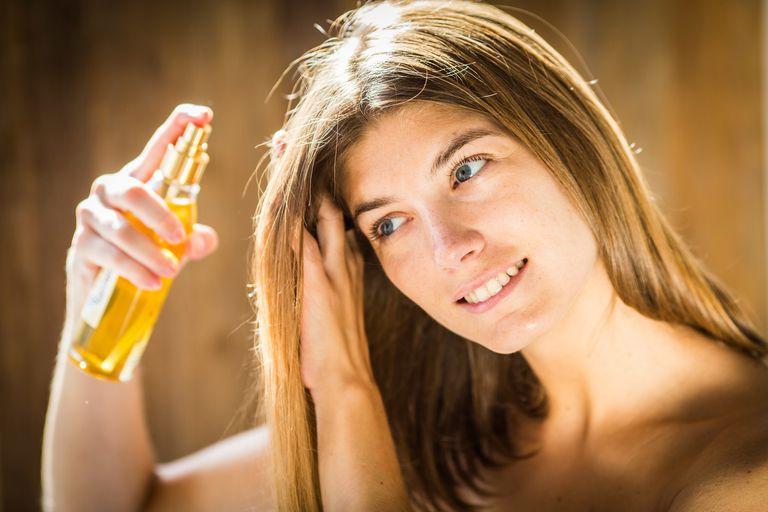Woman applying hair oil