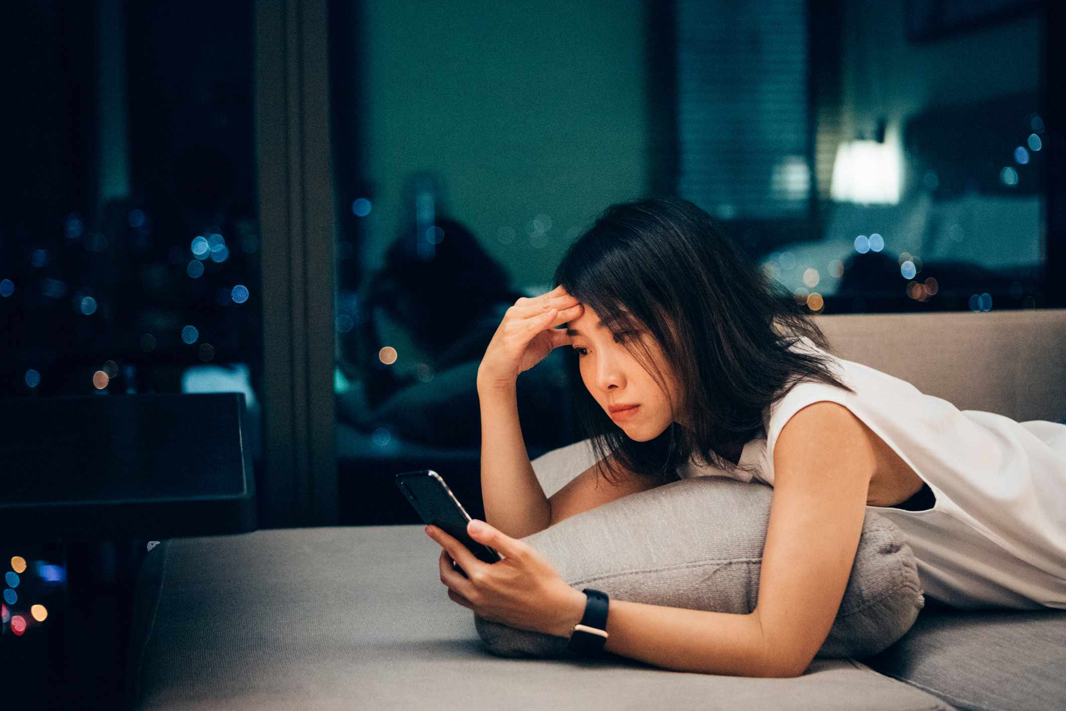 young woman checking her phone at night
