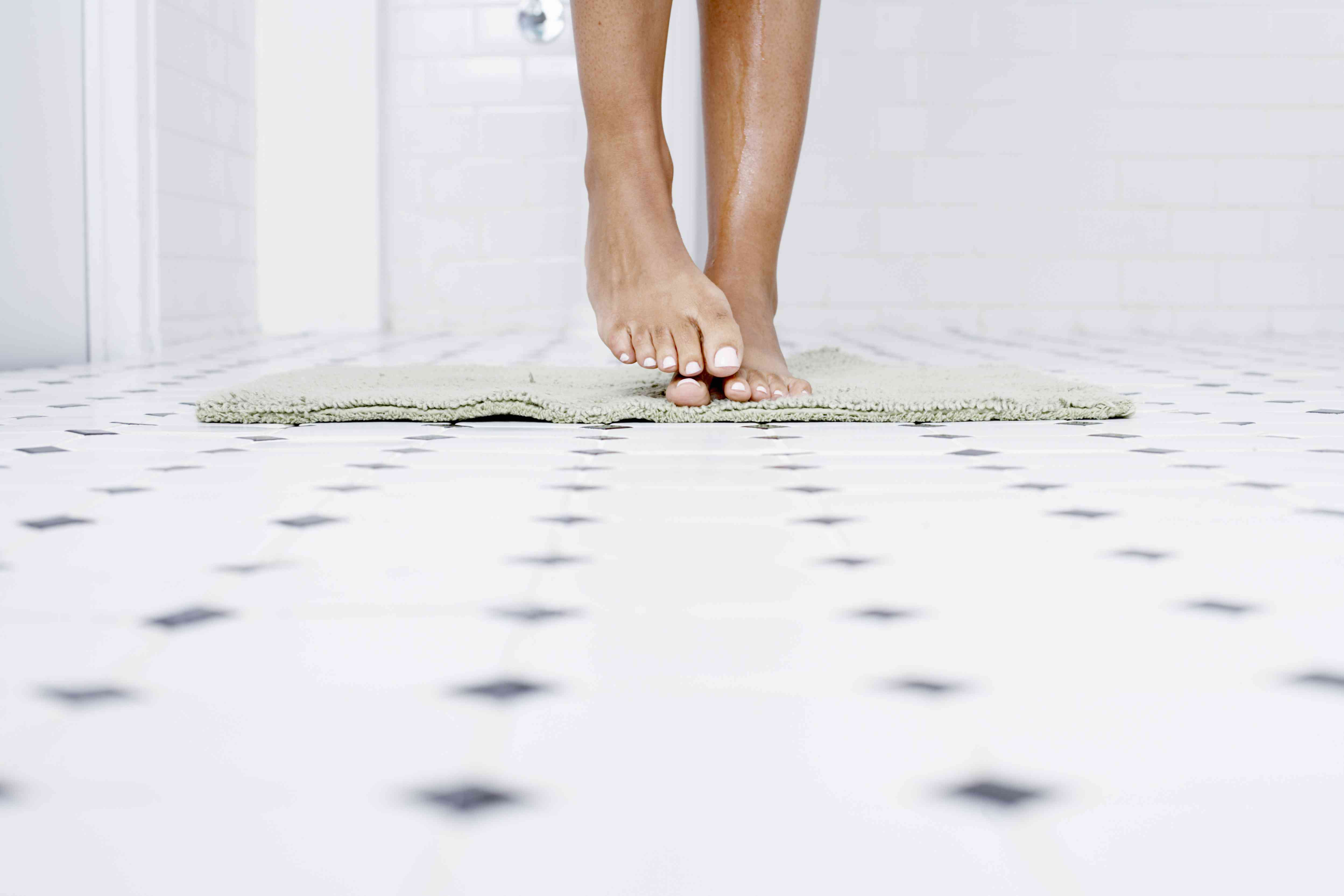 Woman standing on towel in bathroom