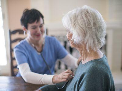 nurse listening to a woman's heartbeat