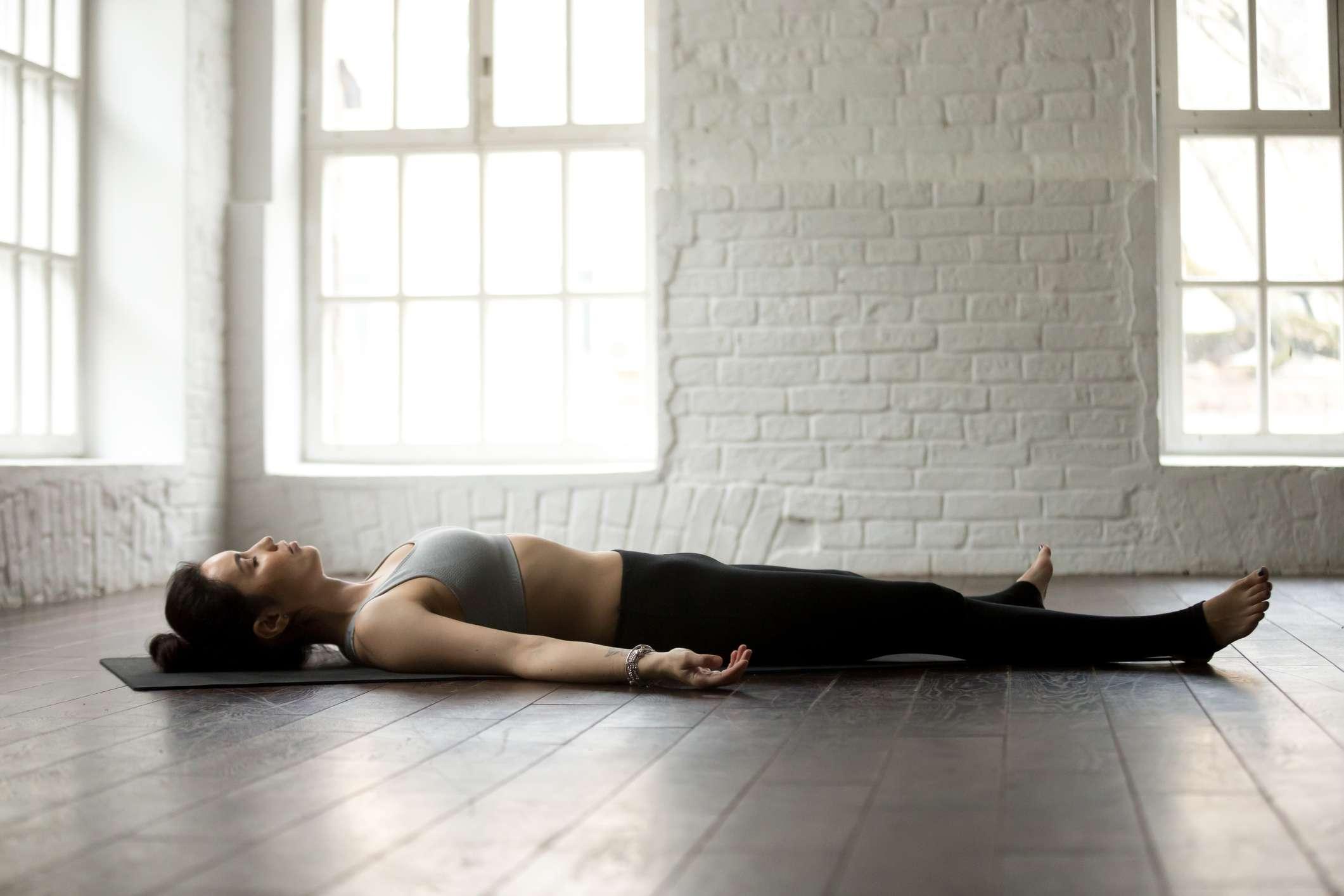 Woman near windows in a bright yoga studio in the Supine position
