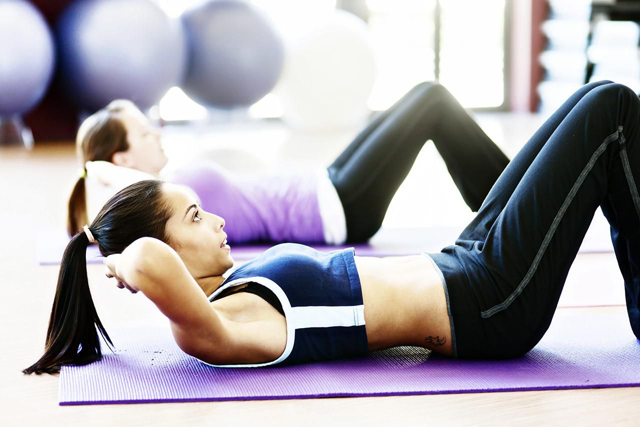 A beautiful fit young woman does sit ups in a gym; another woman does the same in the background.