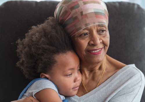 Grandmother with cancer holds grandchild or great-grandchild