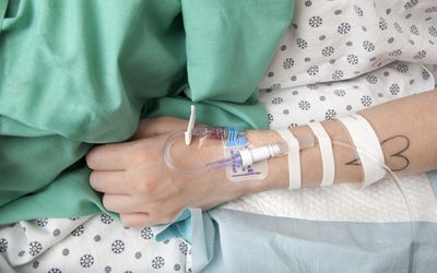 Woman with IV in hospital bed