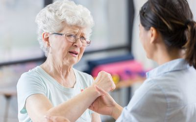 Senior patient grimaces as therapist manipulates elbow