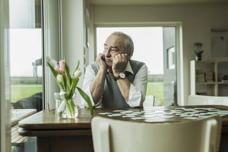 Sad man sitting at a table and looking out a window
