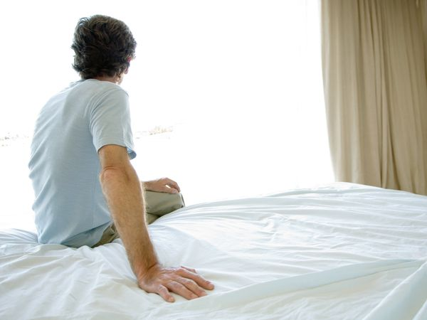 Mature man sitting alone on bed, looking out window