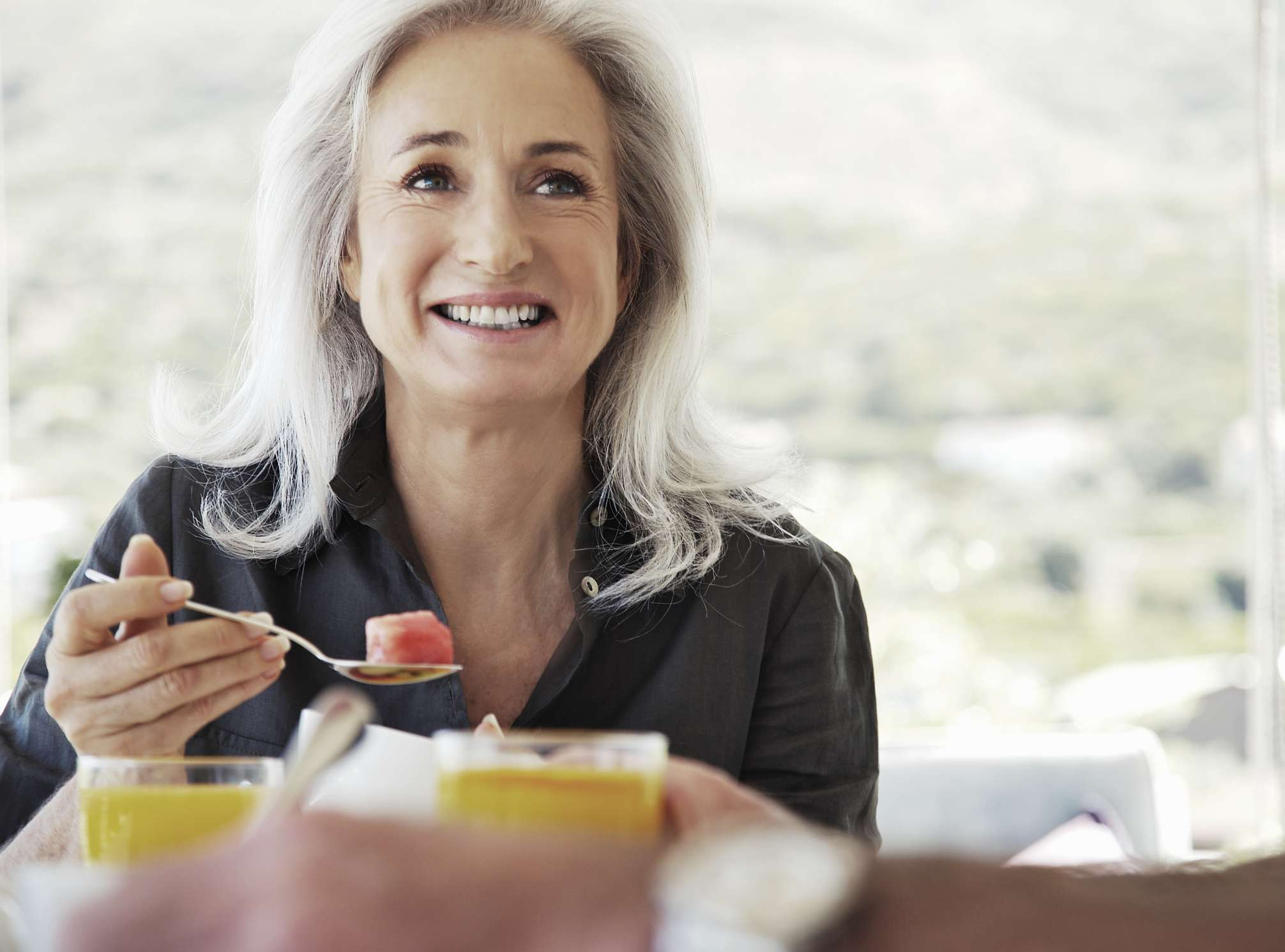 mature woman eating breakfast