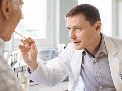 Otolaryngologist examines sore throat of senior patient