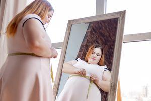 Nice chubby young woman measuring her waist