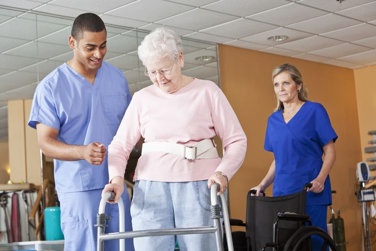 Healthcare workers with senior woman using walker
