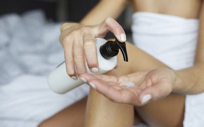 Woman putting on lotion