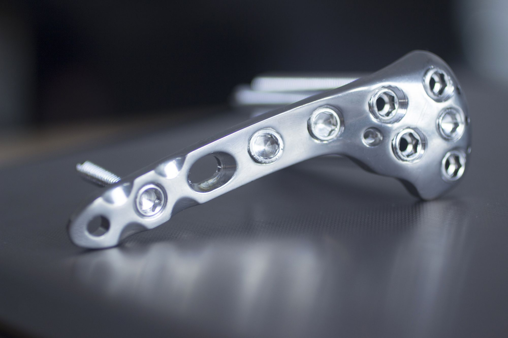 Trauma and orthopedic surgery metal implant with screws with reflection and bokeh light effect