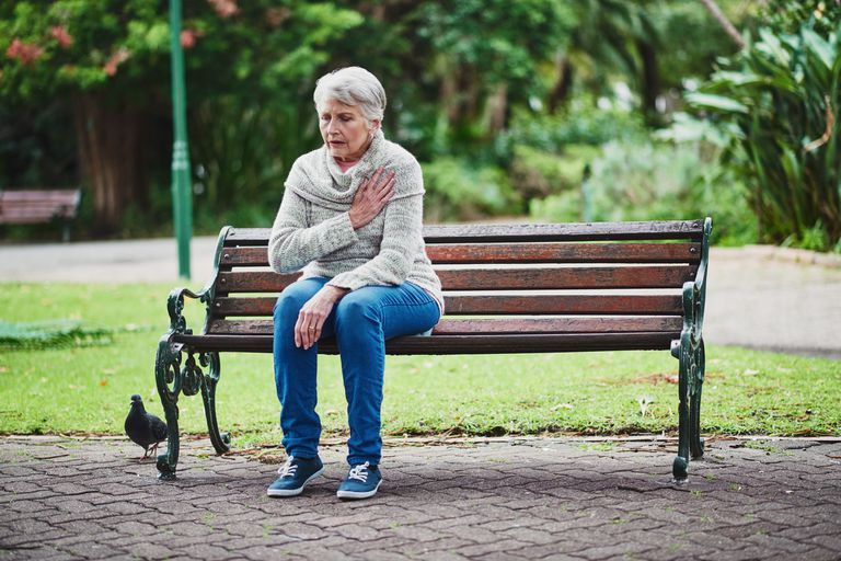 A woman sitting on a park bench with heart pain