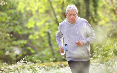Older man running through woodland and flowers